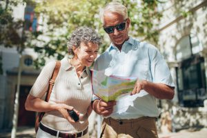 Middle aged couple using city map during vacation. Senior couple looking at a map while sightseeing.