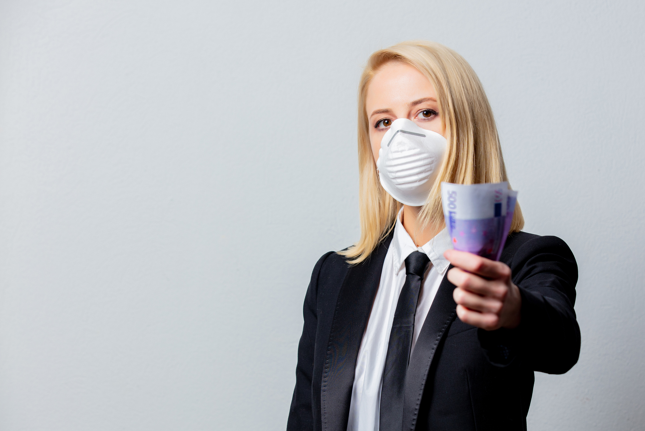 Businesswoman in black suit and face mask with money on grey background